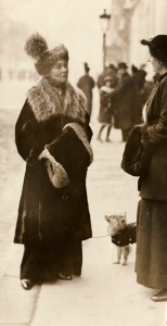 Emmeline Pankhurst talking to Grace Roe, c.1912. Emmeline Pankhurst and Grace Roe talking in the street; manuscript inscription on reverse in Olive Bartels' writing 'Mrs Pankhurst with Christabel's little dog talking to Grace Roe in France (probably Paris)'. Part of the image has torn away. LSE, 7JCC/O/02/148